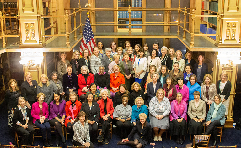 More than 60 female ambassadors pose together seated and standing in a photo in Riggs Library.