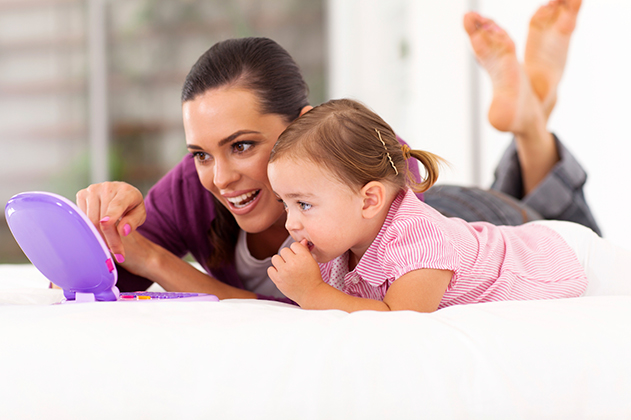 Woman and toddler lay on their stomachs watching a small screen device together