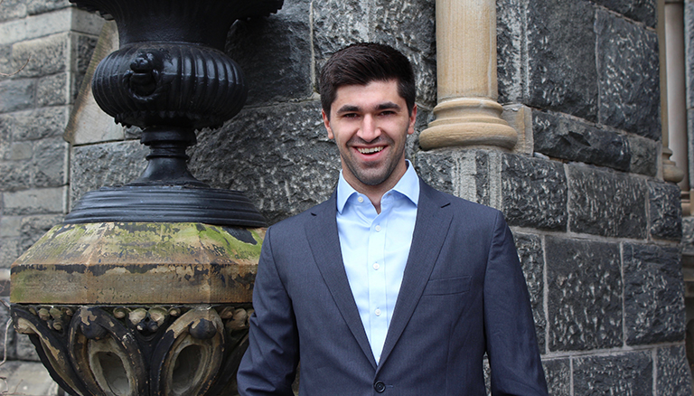 Tomás Álvarez Belón stands to the side of Healy Hall with a smile