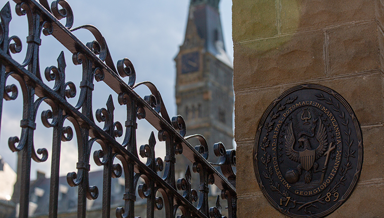 front iron gates of Georgetown with seal on concrete wall and Healy building spire in the background
