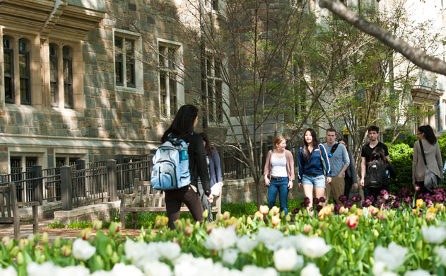 Students, wearing backpacks, walk to class.