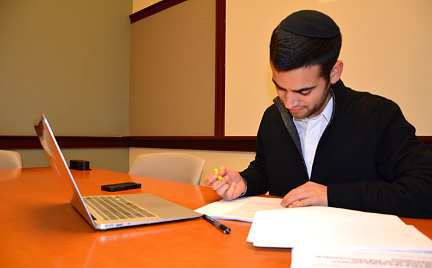 Daniel Bral sits at a table and highlights a paper.