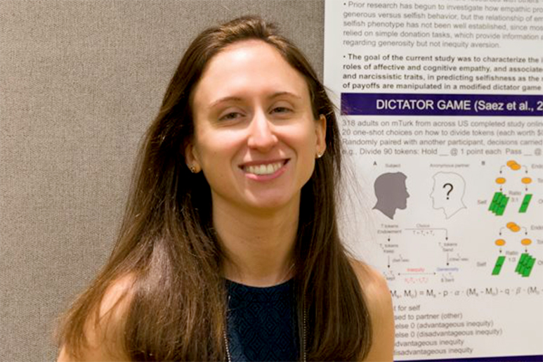Kristin Brethel-Haurwitz smiles while standing in front of a psychology poster.