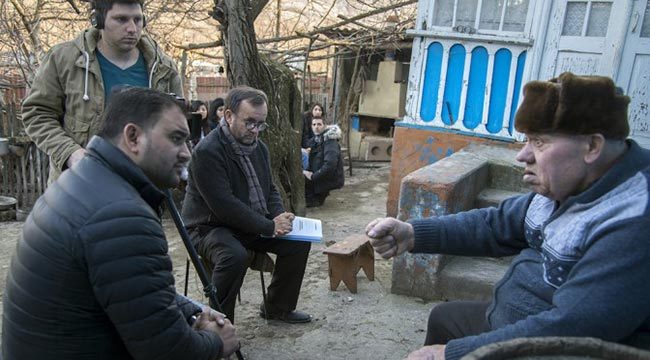Rev. Patrick Desbois interviews Moldova residents with students surrounding him