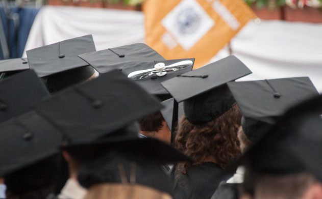 Black graduation caps atop the heads of college graduates at Georgetown University, one has a propellor decoration