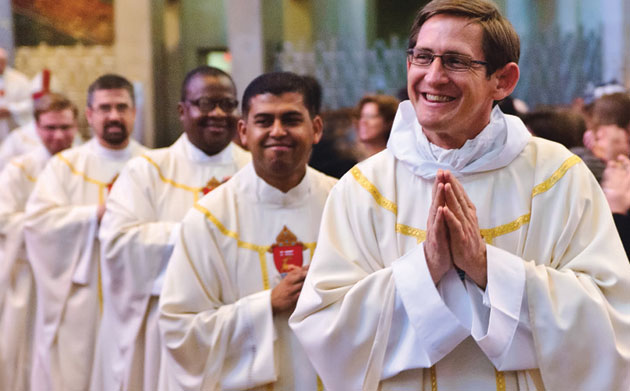 A priest smiles while holding his hands in prayer while other priests process behind him