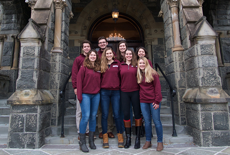 Eight students dressed in maroon shirts stand on the steps of Healy Hall.
