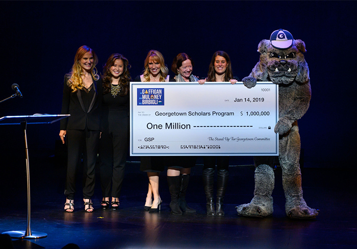 A group of Georgetown alumni stand with the school mascot on stage holding up a check for $1 million.