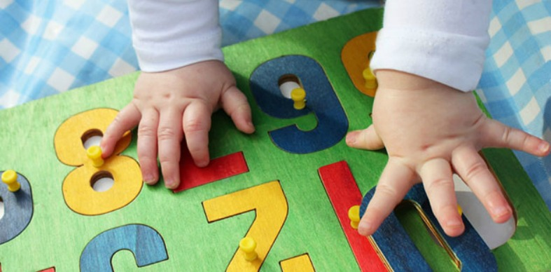 A photo of a baby's hands on top of a colorful puzzle.