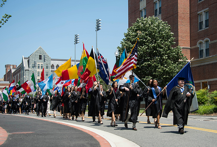 Graduating seniors marching with flags representing their countries