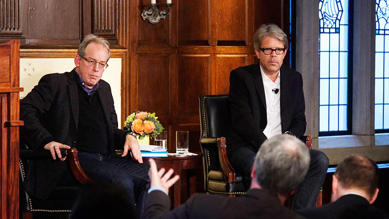 Paul Elie and Jonathan Franzen sit on stage listening to a member of the audience who is gesturing with one hand