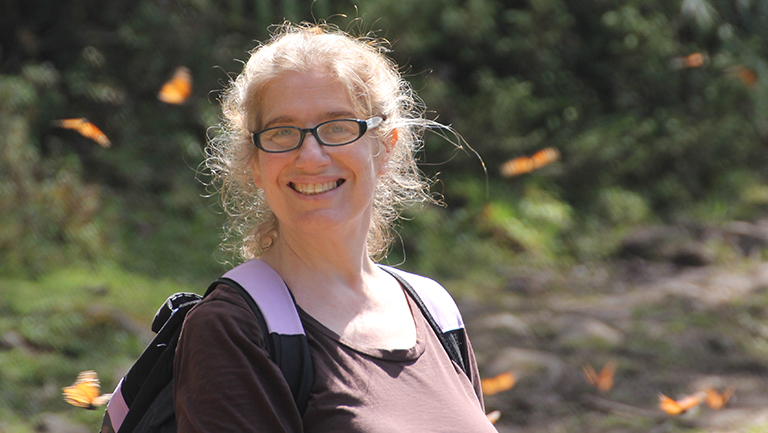 Leslie Ries with monarch butterflies hovering around her