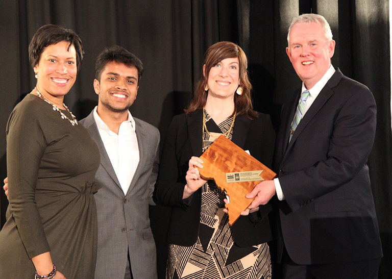 D.C. Mayor Muriel Bowser, stands with Sahil Nair and Tommy Wells as Audrey Stewart holds up an award in the center of he group.