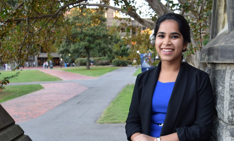 Devika Ranjan poses with part of Healy Hall in the background