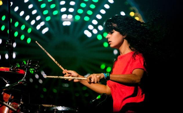Kiran Gandhi's hair flies as she plays the drums