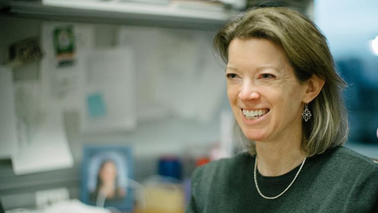 Heidi Elmendorf standing next to her desk