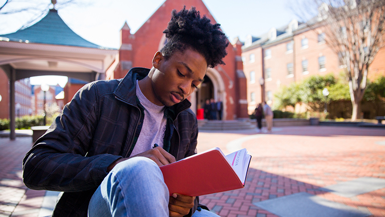 Emmanuel Thomas writes in a notebook while sitting down with Dahlgren Chapel in the background.