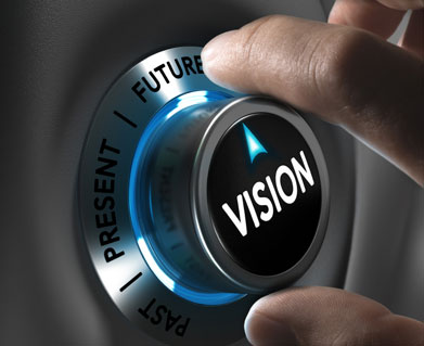 """A hand turns a dial with the words """"Past,"""" """"Present,"""" and """"Future"""" on it; the word """"VISION"""" is emblazoned on the dial's center."""