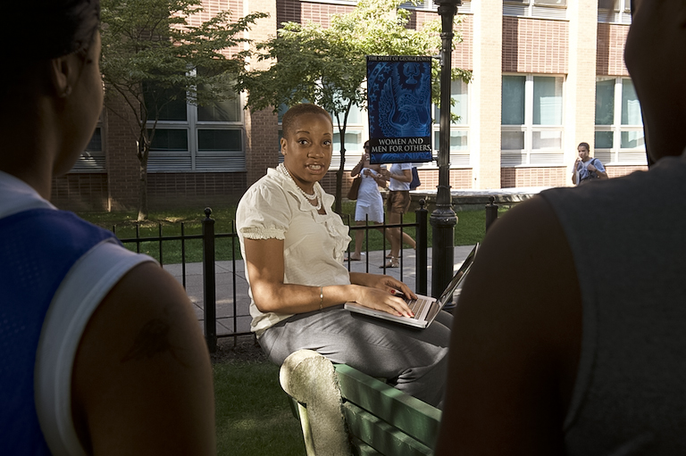 Pamela Nwaoko sits on a stone bench talking while typing with a laptop in her lap.
