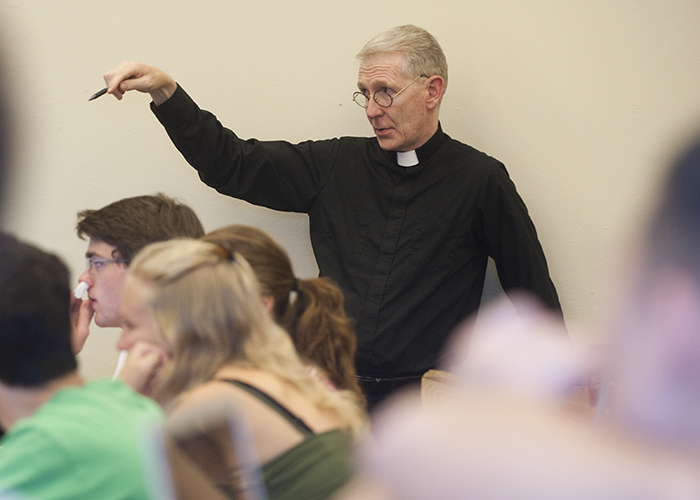 Rev. Dennis McManus gestures while teaching students in class at Georgetown.