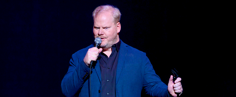 Jim Gaffigan speaks into the microphone while on stage.