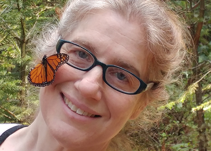 Leslie Ries, wearing glasses outside with butterfly on her cheek