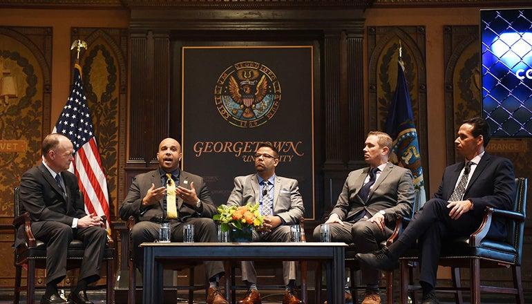John J. DeGioia, Brian Ferguson, George Chochos, Shon Hopwood and Marc Howard on stage with flag and Georgetown University sign