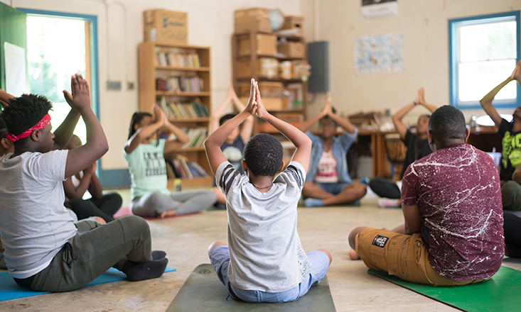students in a circle in a classroom doing yoga poses