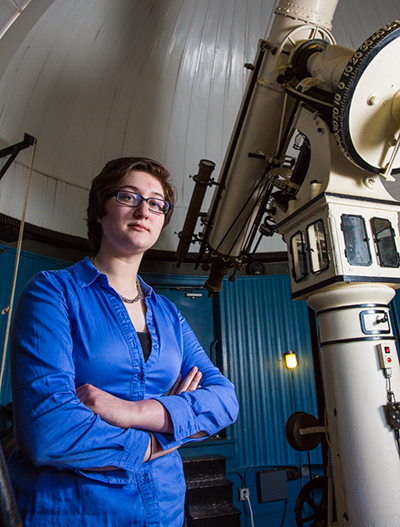 Grace Maglierin stands in the campus observatory near the telescope