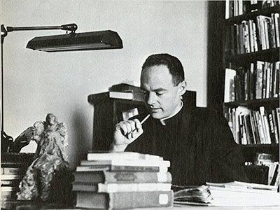 Rev. William McFadden, S.J. sitting at a desk holding pen in 1967