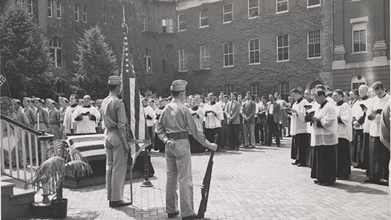 American flag draped over a coffin with another American flag standing near soldiers and priests in Dahlgren Quadrangle at Georgetown