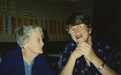 Janet Reno sitting with an elderly woman and smiling into the camera