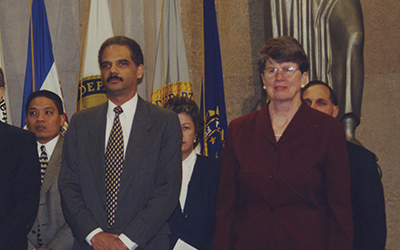 Janet Reno with Eric Holder, standing with others in front of flags