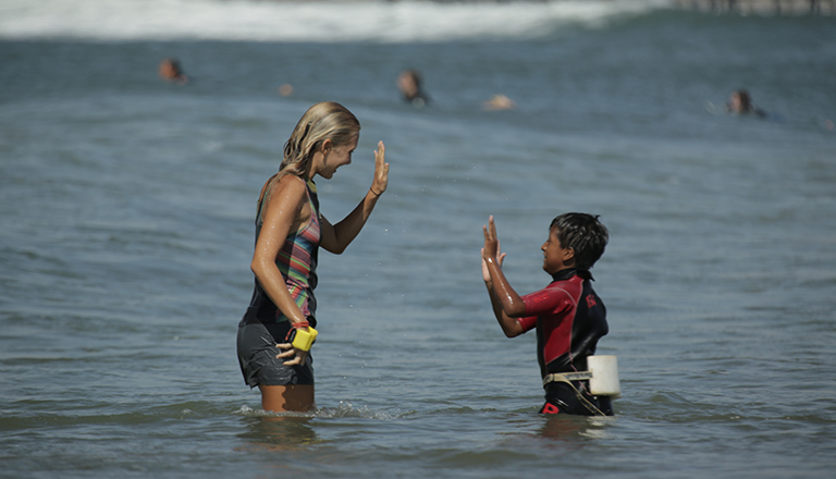 Emi Koch in the ocean high-fiving a young boy