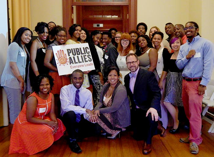 Nakeisha Neal Jones poses with some of her graduating Public Allies students as they hold up a sign that says Everyone Leads