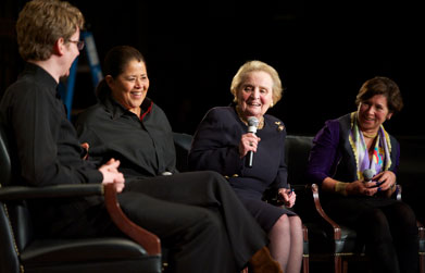 Madeleine Albright speaks on stage in Gaston Hall while Anna Deavere Smith and Joshua Roman look on