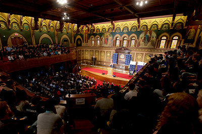 A wide-angle picture of a full Gaston Hall with the audience watching Senator Sanders speak from a podium.