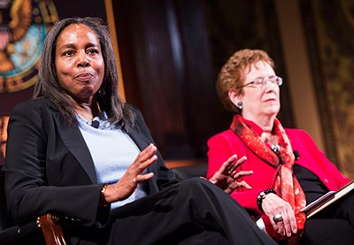 Valerie Babb and Kathleen Lesko, seated onstage at Gaston Hall, make discuss with other panel members.