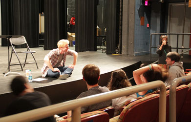 Michael Benz sits on a stage and talks to students who are seated in theater