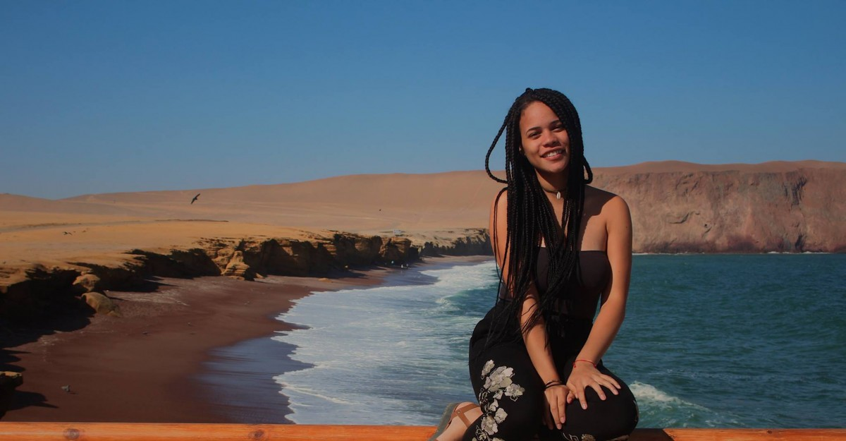 Bianca Uribe sits surrounded by a beach with an expansive blue sky in the background.