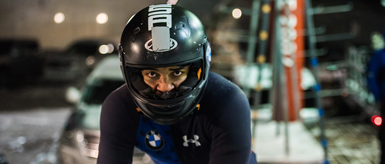 Christopher Kinney stares ahead outfitted in his bobsledding gear