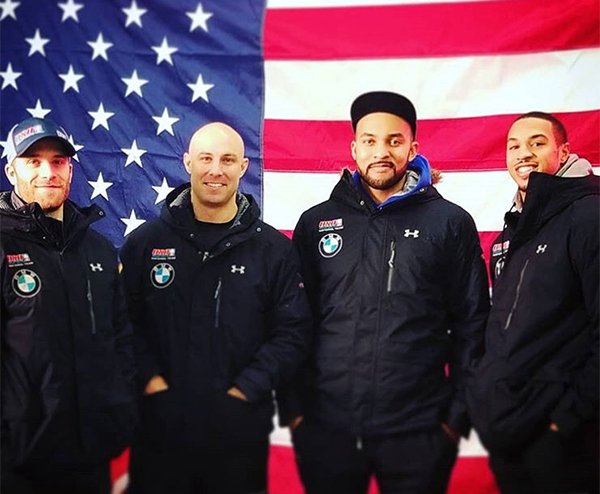 Four Members of the U.S. Olympic Men's Bobsled Team stand in front of the U.S. flag.