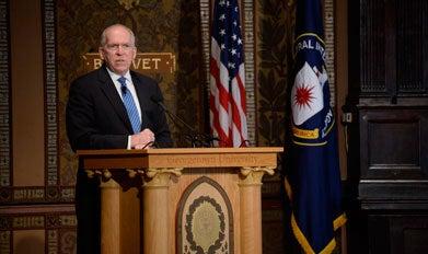 John Brennan speaks behind a podium on Gaston Hall's stage.