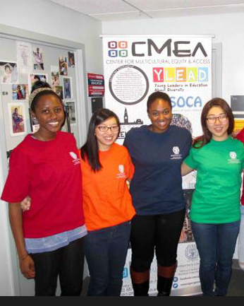 Four CMEA Spring 2016 interns dressed in colorful shirts pose in front of a poster.