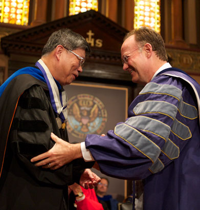 Der-Chen Chang shakes hands with John J. DeGioia in Gaston Hall