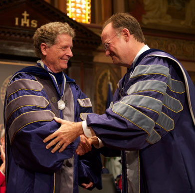 Richard Schlegel shakes hands with John J. DeGioia