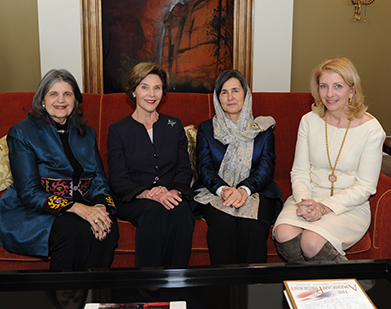 Phyllis Magrab, Laura Bush, Rula Ghani and Catherine Russell, seating on sofa with abstract painting behind them