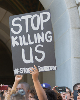"""A protestor holds a black sign with the words """"Stop Killing Us"""" written on it."""
