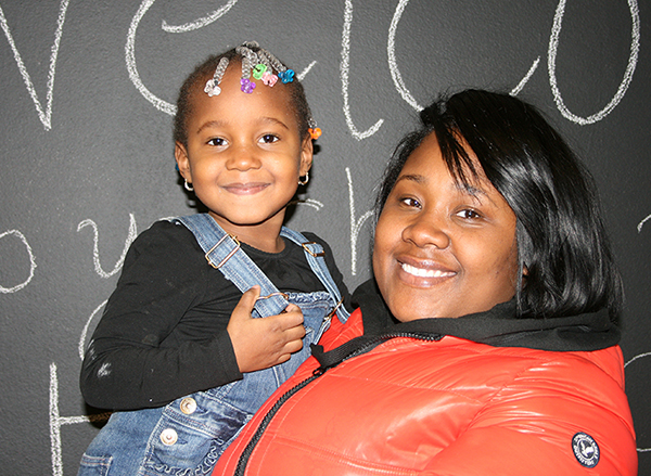 Crystal Jenkins holds her daughter in her arms in front of a chalkboard.