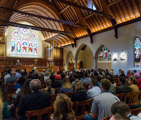 Members of the university community in the foreground sit watching and listening to the archbishop as he stands in front of colorful stained glass under the chapels's wooden arches.